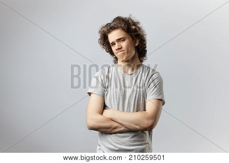 Displeased handsome 20 year old guy having suspicious look pursuing lips not believing some dubious information suspecting his girlfriend of cheating holding arms folded. Horizontal shot