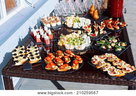 Catering Banquet Table With Different Food Snacks And Appetizers