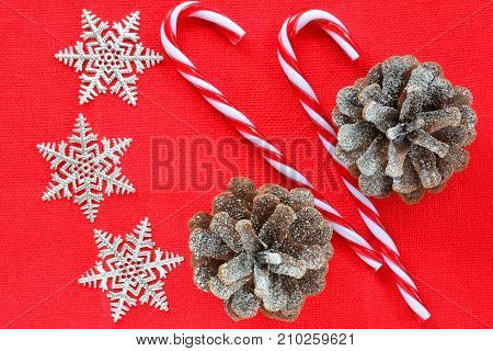 Christmas decorations on textured red background in horizontal format shot from overhead