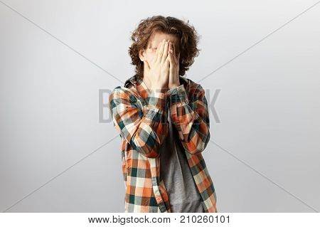 Unrecognizable young man dressed in trendy checkered shirt over grey t-shirt covering face with both hands feeling shy ashamed embarrassed or stressed. Body language and non verbal communication