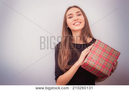 Happy brunette woman holds red christmas gift box and smiling