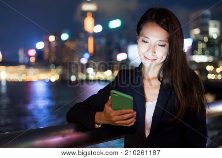 Business woman working on mobile phone in Hong Kong city