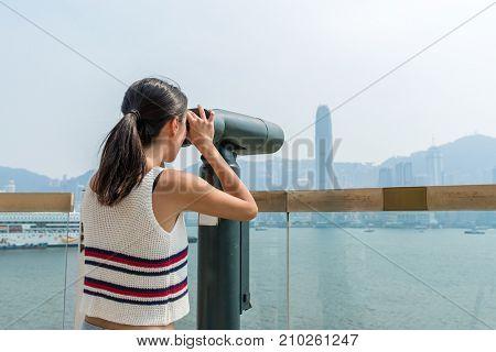 Woman looking though tourist binoculars in Hong Kong city
