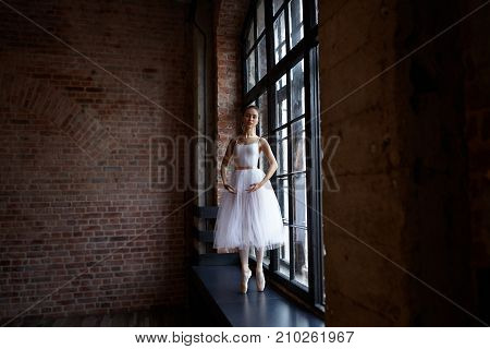 Graceful professional young woman ballet dancer standing on pointes on windwosill at lrage window dressed in white tutu while training in studio with blank copy space wall for your promotional content