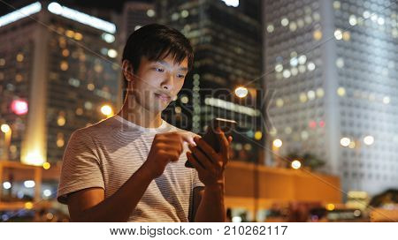 Young man using mobile phone in city at night