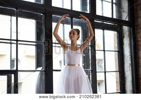 Grace and performance of beautiful girl wearing white ballet skirt and hair gathered in knot dancing at lrage window during class at ballet school having focused expression on her pretty face