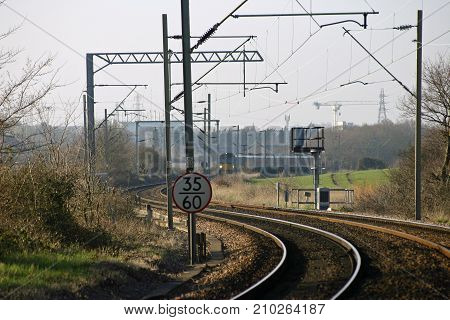 Curved local railway line with electric overhead cables and train in the distance. Background of trees hedges and fields.