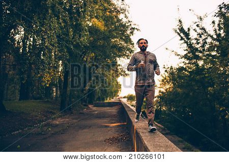 Healthy lifestyle adult sportive man running in the city park Male in headphones and smartphone in hand jogging.