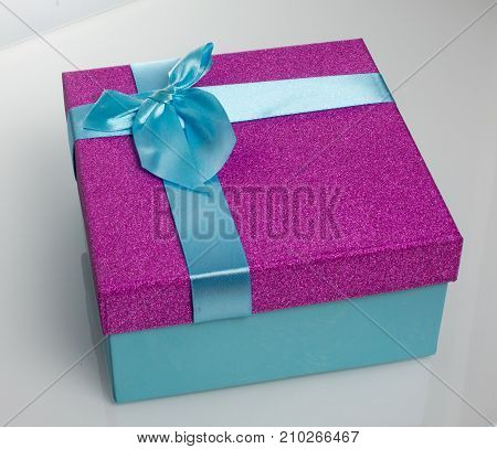 A beautiful gift box in blue, with a purple ribbon and bow. Beautiful christmas card on white background. An unusual postcard.