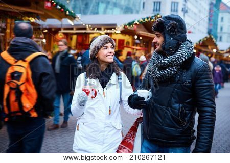 Young couple doing christmas shopping at christmas fair, smiling, drinking hot drinks.