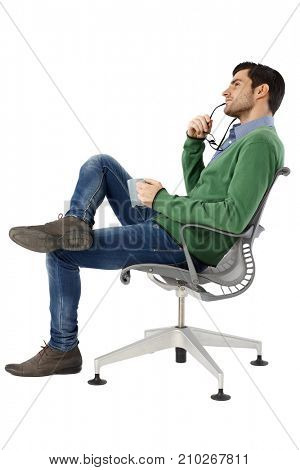 Side view of daydreaming young man sitting in swivel chair. Full size.