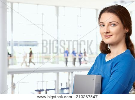 College student girl standing in library lobby in university building, looking at camera smiling.