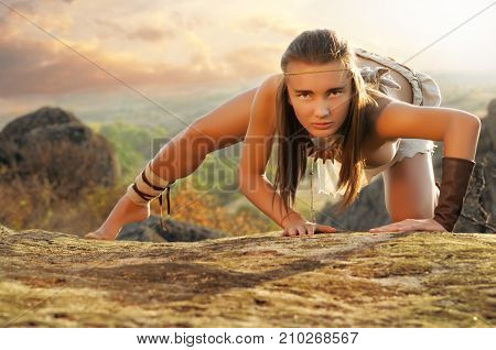 Primitive Woman On A Rock At The Sunset. Amazon Woman