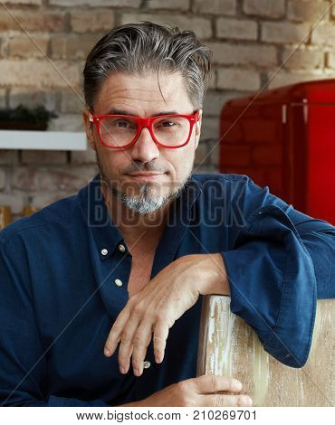 Portrait of an older man. Older man wearing trendy red glasses.