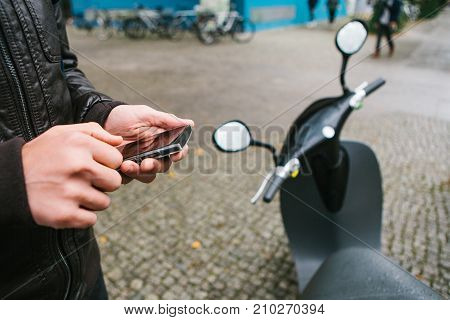 The tourist is going to use the electric scooter through the mobile application in the phone and distally activate it. A popular vehicle in Berlin and Paris
