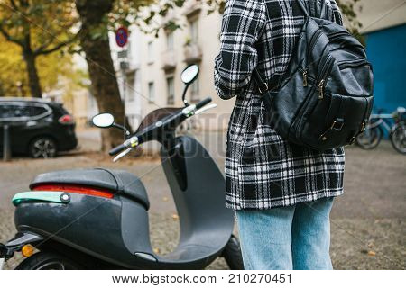 A tourist with a backpack is going to use an electric scooter through a mobile application in the phone and distally activate it. A popular vehicle in Berlin and Paris