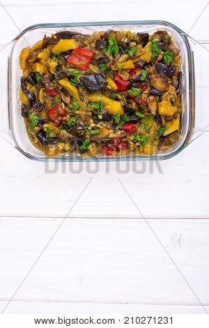 Vegetable saute with eggplant on white wooden background. Studio Photo