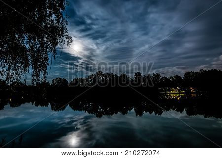 Night scary scene. Full moon above the pond with silhouette of a tree. Dark blue clouds on a sky. Reflections on a water surface.