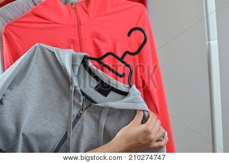 Woman hands picking a sports jacket in the shop.