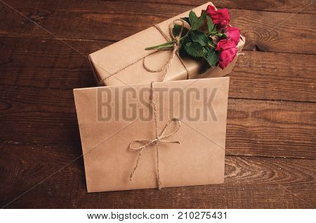 gift wrapped in kraft paper with rose flower at the top near the envelope