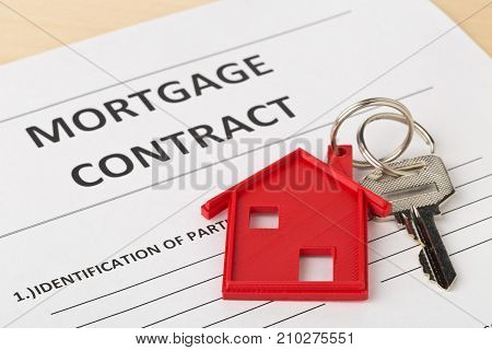 House door key with red house key chain pendant and mortgage contract form on wooden desk - house or apartment rental concept