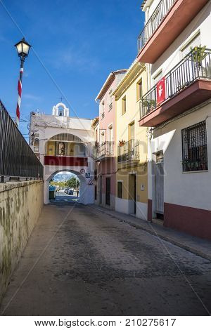 OLIVA, VALENCIA, SPAIN, 15TH JANUARY 2017 - Colourful buildings and gate chapel of Saint Vincent (San Vicente). The city gate is the oldest access route into the medieval city of Oliva Valencia Spain