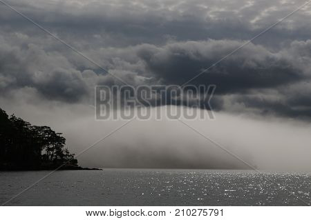 Dramatic, massive fog bank rolling into a San Juan Island, Puget Sound, Washington, under a dark, cloudy sky and over a sparkling sea.