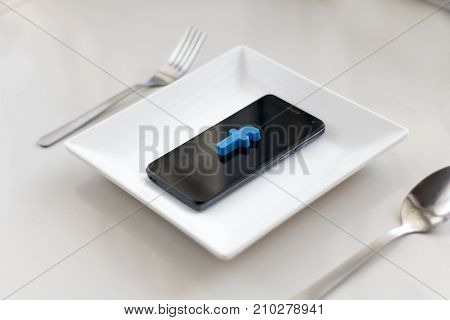 Selangor Malaysia - 19 October 2017: A smartphone with a letter f which symbolised Facebook social networking site was put in an empty plate on a table on October 19 in Selangor.