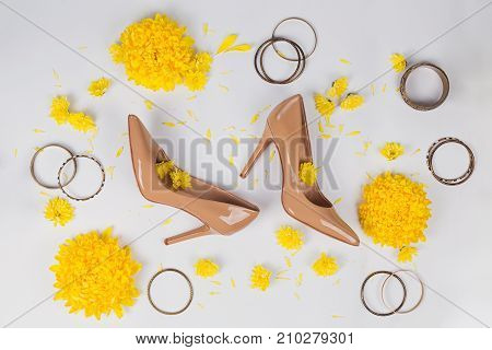 Female workspace with yellow flowers and women's accessories: high heels and bracelets on white background. Flat lay top view office table desk.