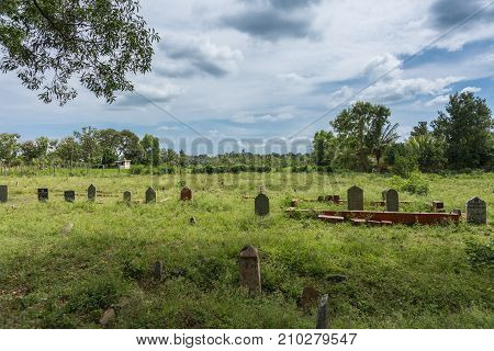 Chikunda India - October 28 2013: Landscape of Muslim cemetery in the village under cloudscape. Short gray and brown tombs with Arabic inscriptions in a sea of green weeds. Green jungle in back.