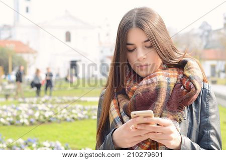 Portrait of a young beautiful woman sending messages with her smartphone. Outdoors.