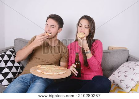 Beautiful young couple drinking beer and eating pizza. Indoors.