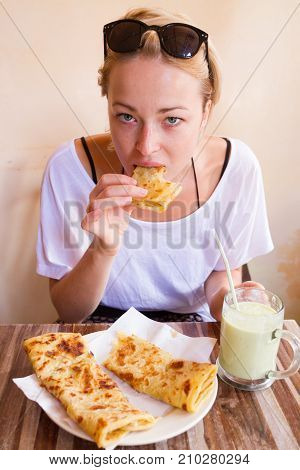 Female tourist eating delicious moroccan brakfast at one of street coffee shops: traditional pancakes with cheese and honey and avocado milkshake.