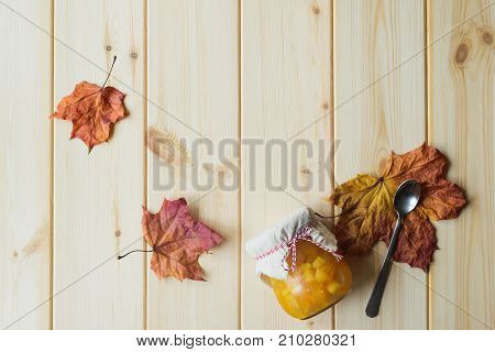 top view of autumn still life of organic pumpkin jam in a jar maple leaves and spoon on natural wood table