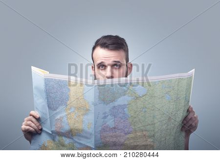 Handsome young man holding map
