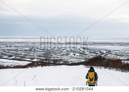 a man with yellow backpack walking on snow mountain in winter, at Iceland