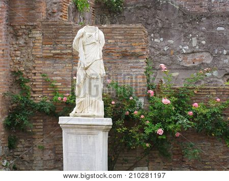 Headless Ancient Statue of Vestal Standing Before Brick Ruins and Roses in Rome