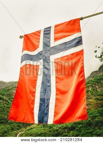 norwegian flag outdoor on green nature mountains in the background