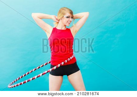 Fitness activity healthy lifestyle. Young blond woman doing exercise with hula hoop on blue