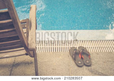 Wooden chair and orange slippers in the summer holiday