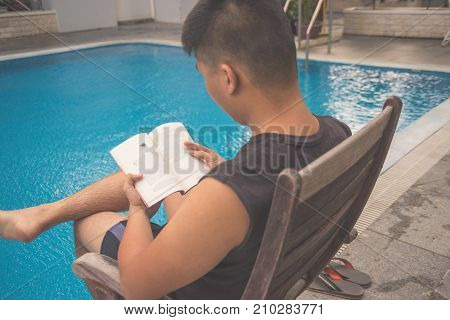 Man reading book at the swimming pool in holiday vacation