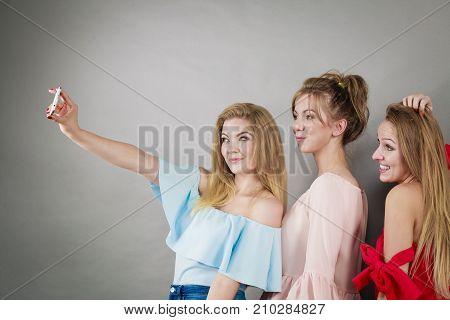 Fashionable women taking selfie self picture using smartphone having fun enjoying friends time.