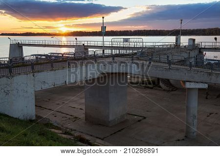 Sunset on the Volga and the old shabby concrete structures of the river station of Samara city. Russia.