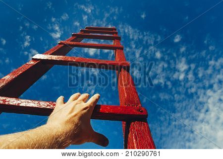 Hand Of Man Reaching For Red Ladder Leading To A Blue Sky. Development motivation Career Growth Concept