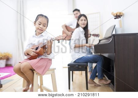 Asian Family,daughter Playing Ukulele,father Playing Guitar,mother Playing Piano