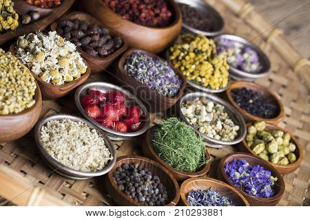 Natural medicine theme. Herbs, berries and flowers in bowls on wooden table.