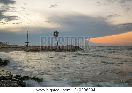 HAIFA ISRAEL - OCTOBER 16 2017: Sunset scene at the Bat-Galim beach with local fishermen in Haifa Israel