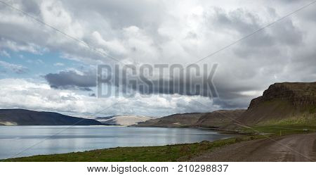 the austere Icelandic landscape with the mountains and the fjords and the ocean in the background