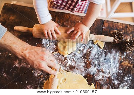 Unrecognizable man and toddler boy making cookies at home. Father and son baking gingerbread Christmas cookies.