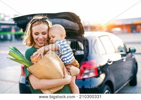 Beautiful young mother with her little baby son in front of a supermarket, holding paper shopping bag. Woman with a boy standing by the car.